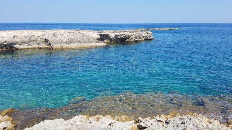 与深蓝色海的西西里人的岩石海岸线 免版税库存图片