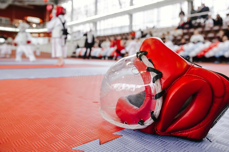 与清楚的塑料面具的红色战斗的盔甲在左边的地板上在前景 和服的两个男孩在空手道的背景 免版税库存图片