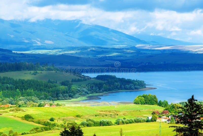 与清楚的山湖和绿色和黄色草甸的田园诗夏天风景 中欧 库存照片