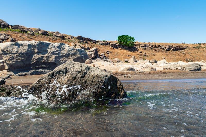 与清楚的水和波浪的岩石海滨 免版税库存照片