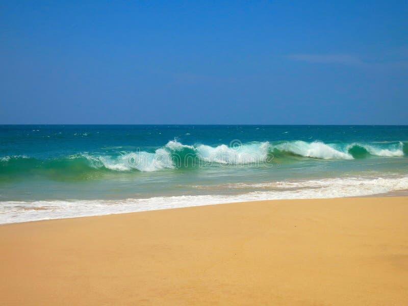 与清楚的沙子和蓝色波浪, Koggala,斯里兰卡的空的海洋海滩 库存图片