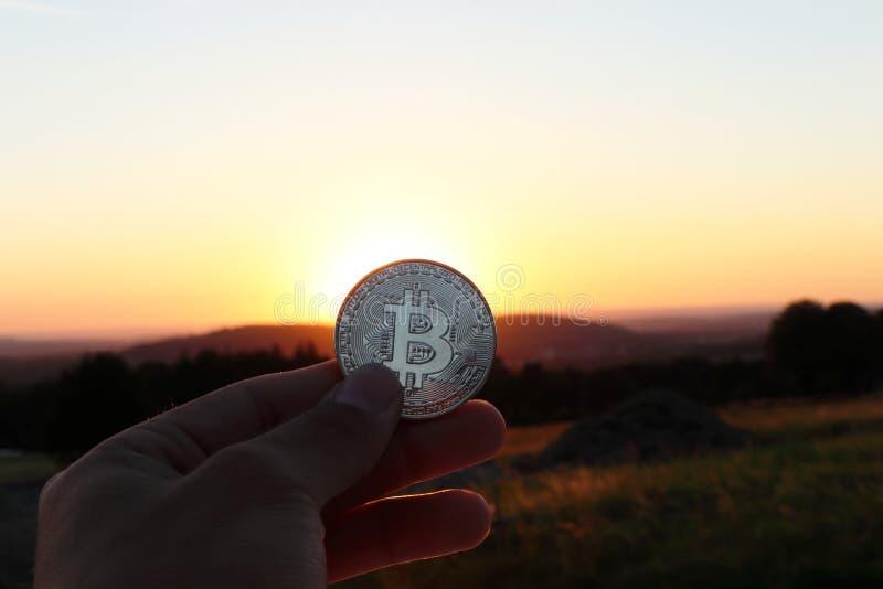 与清楚的蓝天和日落的一银色bitcoin 并且与美丽的草甸 库存照片