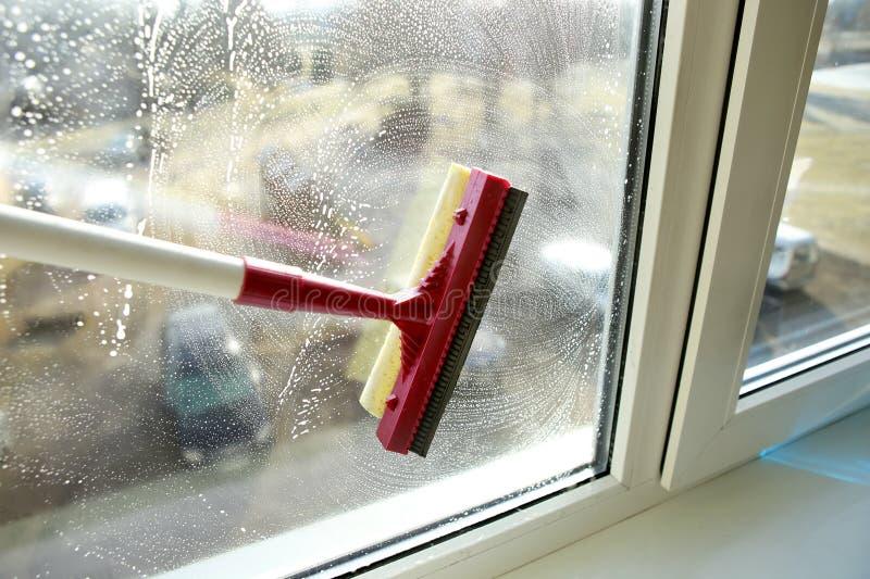 与清洗玻璃的橡皮刮板的肥皂的窗口 免版税库存照片