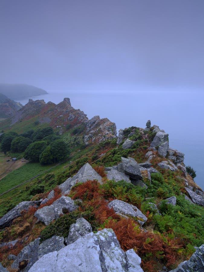 与清除的海薄雾的夏天日出在岩石谷,在北德文区海岸的Lynton附近在Exmoor国民内 免版税库存图片