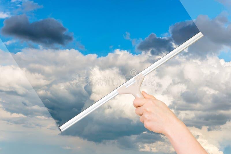 与清洗天空的橡皮刮板的清洁窗口 免版税图库摄影