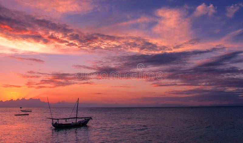 与渔单桅三角帆船的紫外日落 免版税库存图片