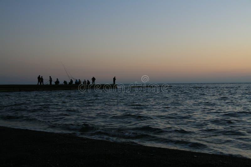 与渔夫剪影的海景  免版税库存照片