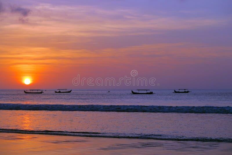 与渔夫` s小船剪影的美好的红色太阳日落,库塔海滩,巴厘岛 库存图片