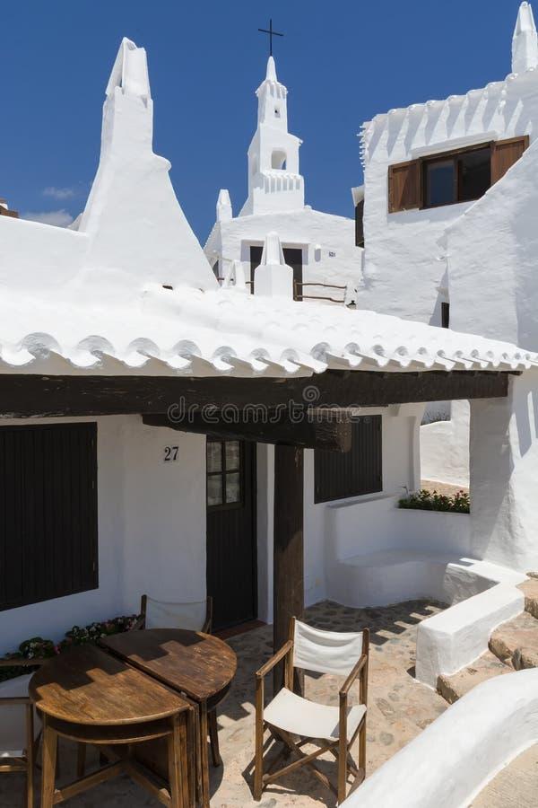 与渔村的钟楼, Menorca,西班牙的看法 免版税库存图片