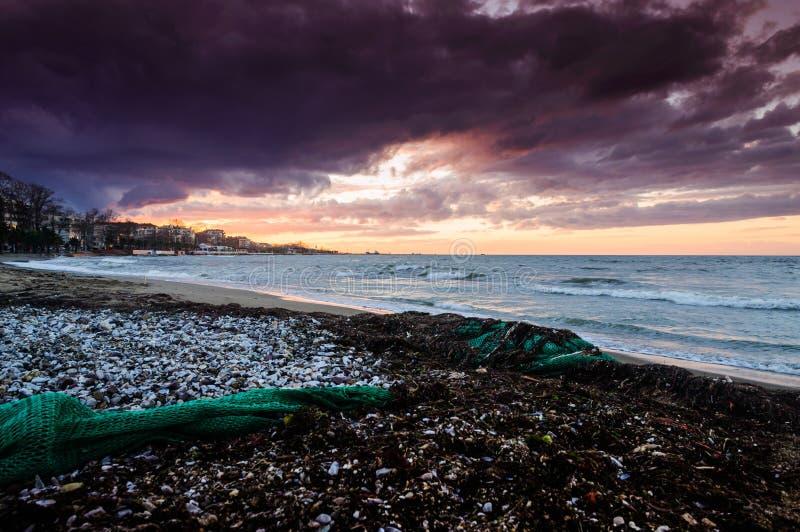 与渔网的海滨日落在沙子 免版税库存图片