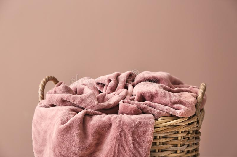 与温暖的格子花呢披肩的柳条筐在颜色背景 图库摄影
