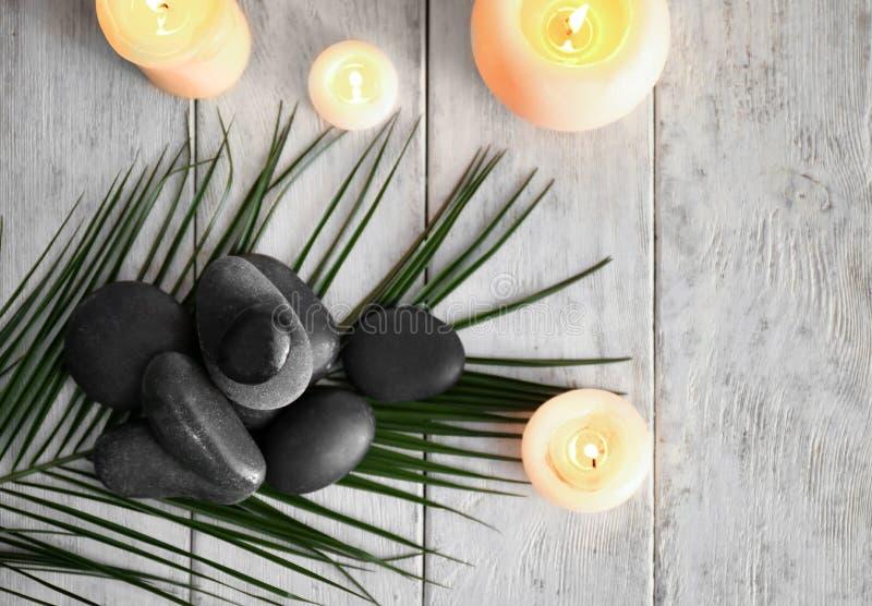 与温泉石头和灼烧的蜡烛的美好的构成在木背景 免版税库存照片