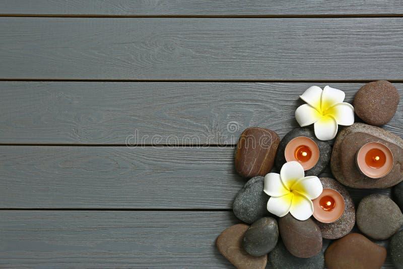 与温泉石头和花的平的被放置的构成在灰色木背景 免版税图库摄影