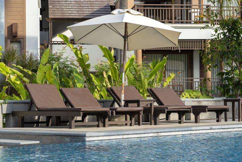 与游泳场、太阳懒人和棕榈树的美丽的热带海滩 免版税库存图片