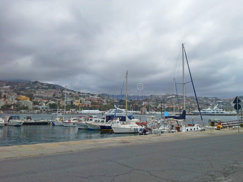 与游艇和小船的海海湾多云天在圣雷莫,意大利,从城市圣雷莫,意大利语里维埃拉的看法 免版税库存照片