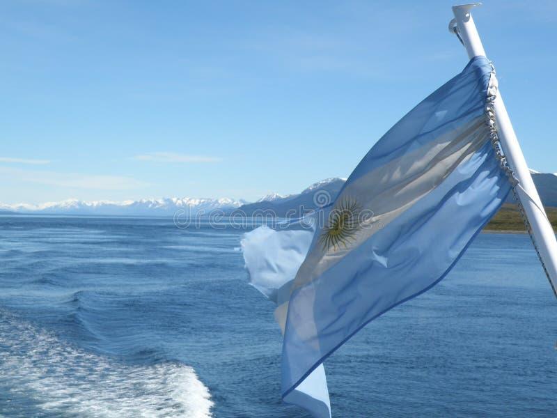 与湖的阿根廷在后面的旗子和山 免版税库存照片