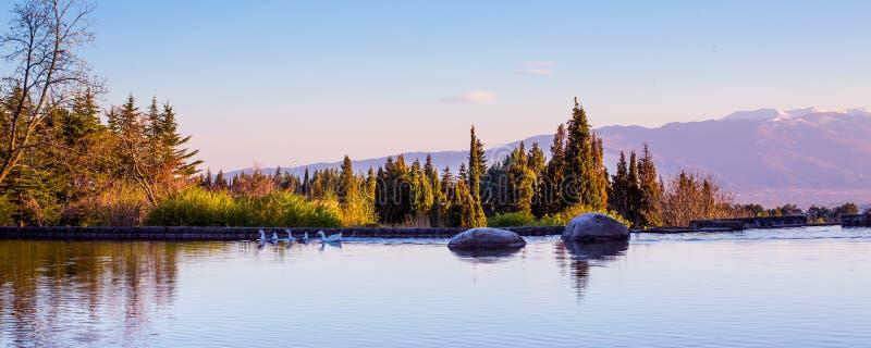 与湖,石头的美好的全景背景 免版税库存照片
