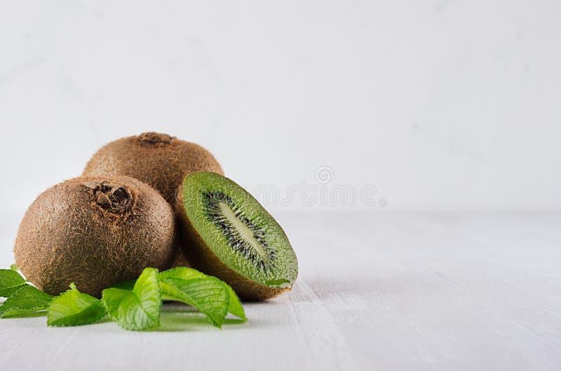 与湿切片部分,在白色木背景的年轻叶子的水多的成熟绿色猕猴桃 食物健康素食主义者 免版税图库摄影