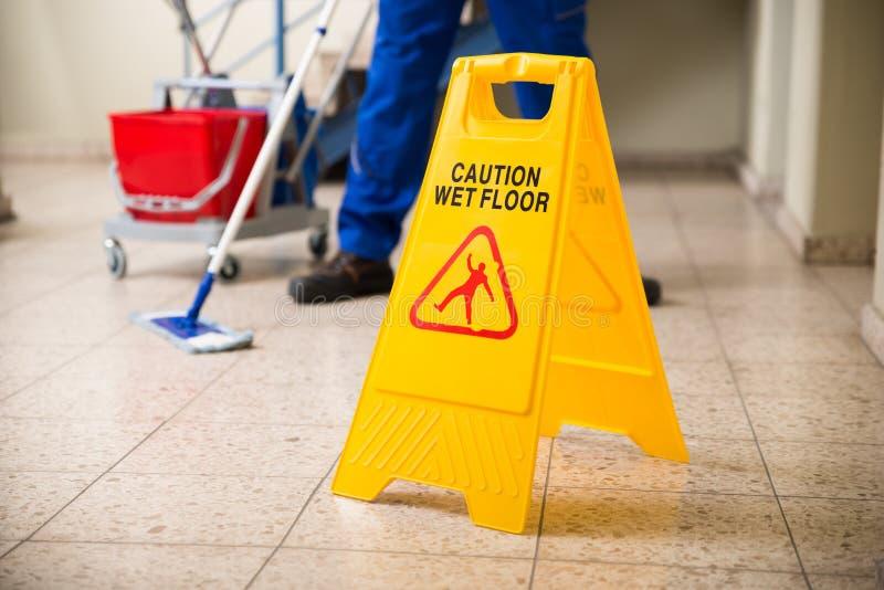与湿地板小心标志的工作者擦的地板 免版税图库摄影