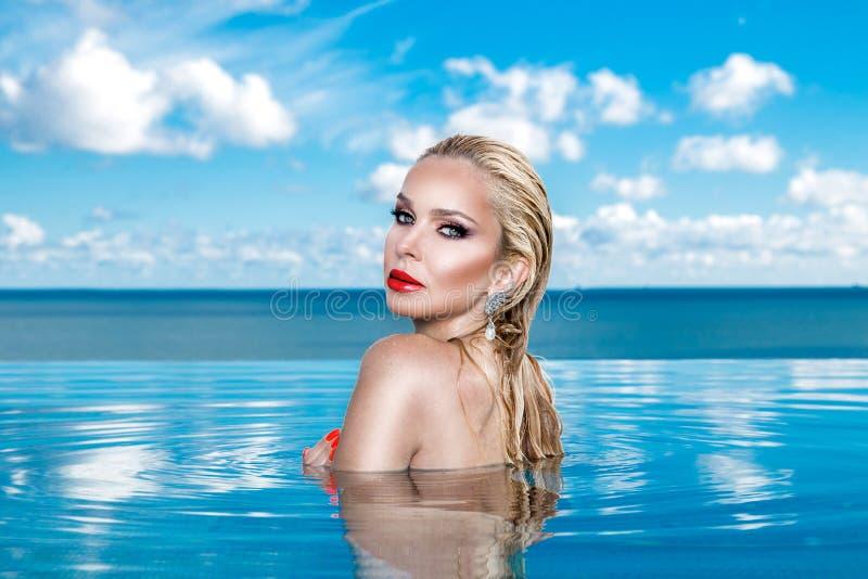与湿坐在水池的头发和典雅的构成的美好的白肤金发的妇女模型 图库摄影