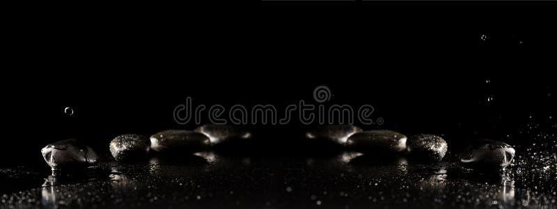 与湿玄武岩按摩石头的温泉背景与水滴 免版税图库摄影