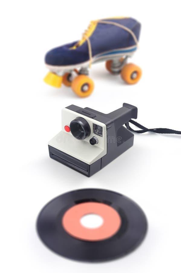 与溜冰鞋和乙烯基- 80的老快速照相机 免版税图库摄影