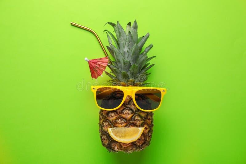 与滑稽的面孔的菠萝由太阳镜和柑橘切片制成当夏天鸡尾酒在颜色背景 免版税库存照片