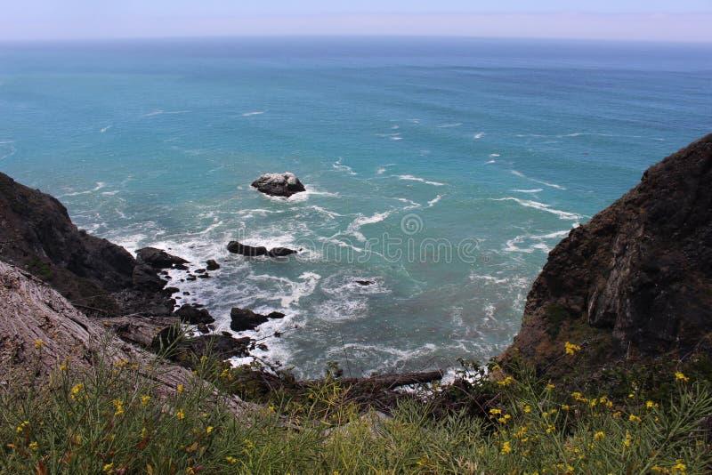 与滚动入岸的波浪的岩石海岸线 库存图片
