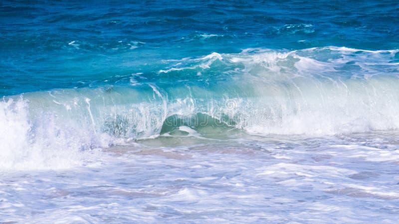 与滚动在一个平安的海滩的泡沫的波浪 库存图片