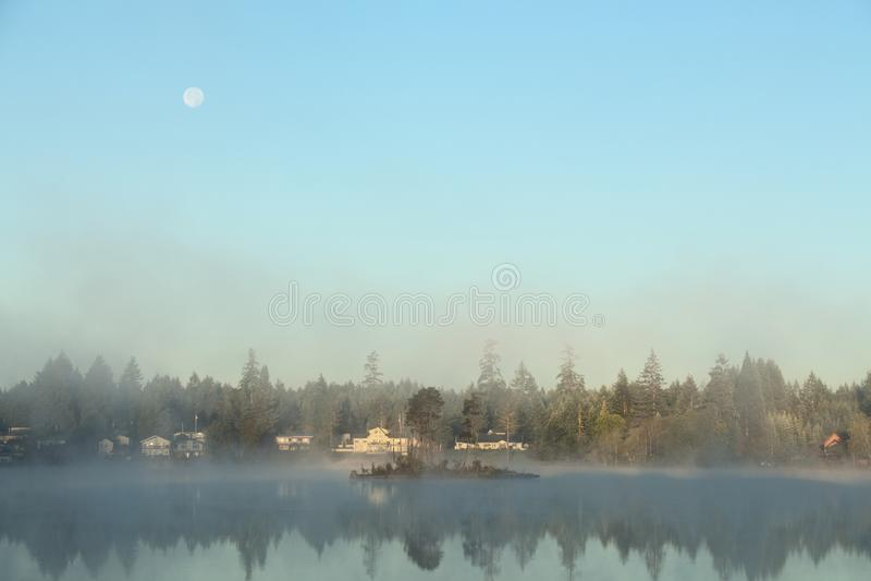 与满月的有雾的早晨在湖 免版税库存图片