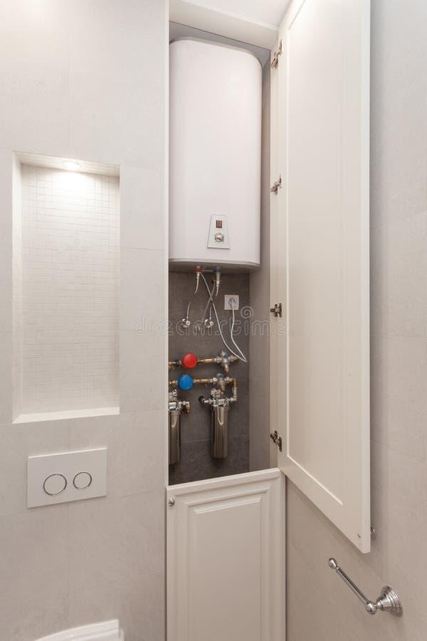 与滤水器的电锅炉在白色浴室 免版税库存图片