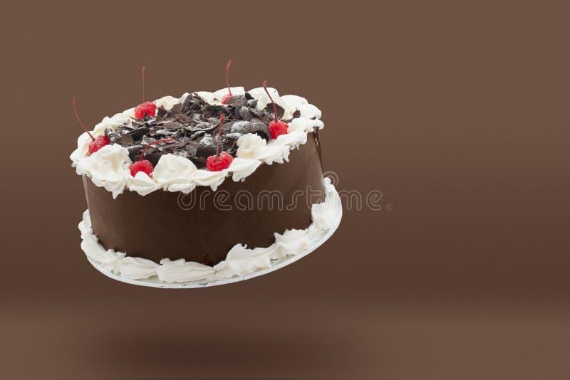 与漂浮在与拷贝空间的棕色背景上的奶油和樱桃的巧克力蛋糕 库存图片