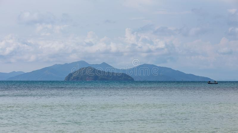 与漂浮在有明亮的天空的海的地方渔夫小船的山在背景中下午在酸值Mak海岛在桐艾府 免版税库存图片