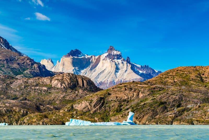 与漂浮在美丽的山前面的湖灰色的冰山的美好的风景 库存图片