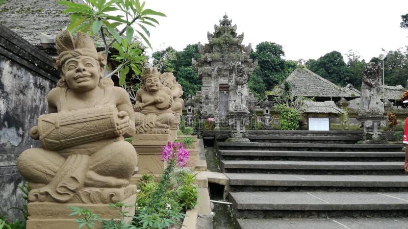 与演奏巴厘语的人雕象的传统巴厘语建筑学kori agung gambelan在penglipuran村庄巴厘岛 免版税库存照片
