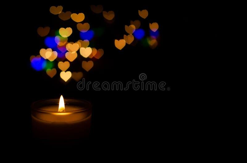 与火焰和五颜六色的爱形状bokeh的白色芳香玻璃蜡烛 免版税图库摄影