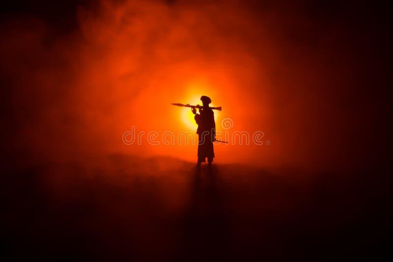 与火箭筒的军事战士剪影 E 与在战争雾天空背景,战士的军事剪影场面战斗 免版税库存照片