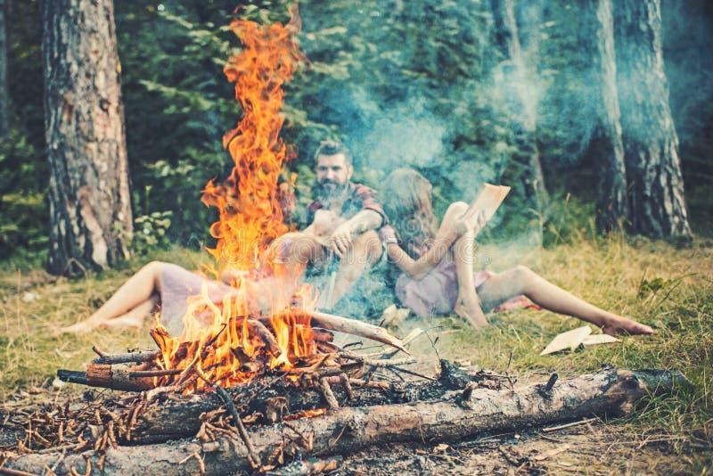 与火花的篝火背景的火焰和人们 在阵营的火烧伤 朋友在营火抽烟放松  野营 免版税库存图片