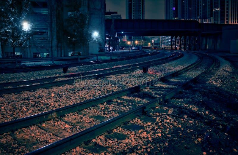 与火车桥梁的城市街市铁路轨道在晚上 免版税库存照片