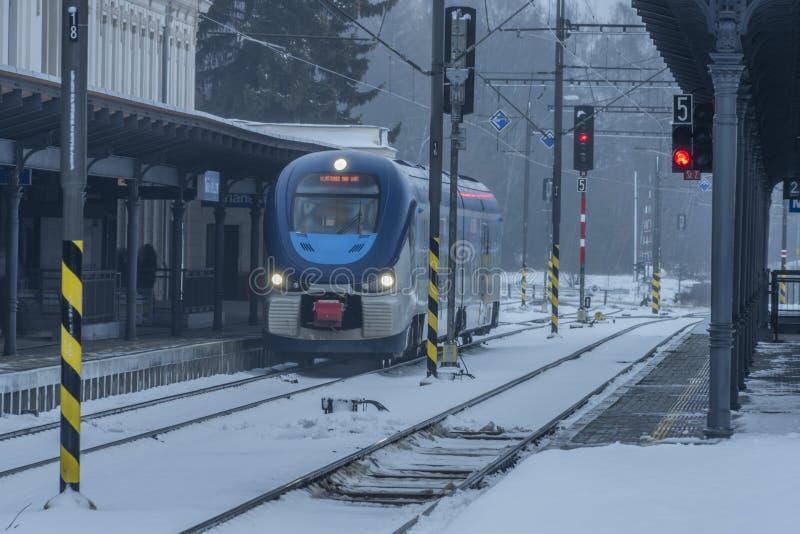 与火车的驻地玛丽亚温泉市在黑暗的雪冬日 免版税库存照片