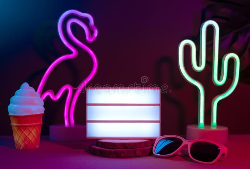 与火鸟、仙人掌、太阳镜和空白的灯箱的夏天项目有霓虹桃红色和蓝色光的在桌上与monstera叶子 ?? 库存照片