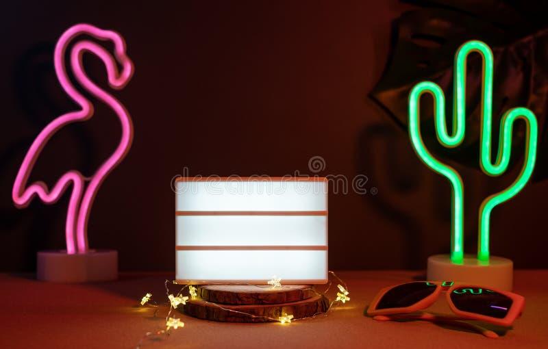 与火鸟、仙人掌、太阳镜和空白的灯箱的夏天项目有霓虹桃红色和蓝色光的在桌上与monstera叶子 ?? 免版税图库摄影