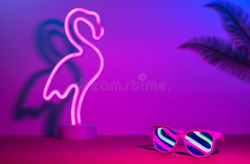 与火鸟、棕榈叶、太阳镜便餐霓虹桃红色和蓝色和绿灯的夏时在与拷贝空间的桌上 ?? 库存图片