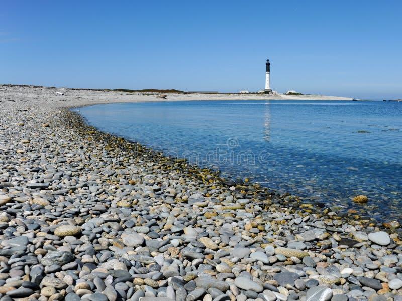 与灯塔的石渣海滩在背景中 免版税图库摄影