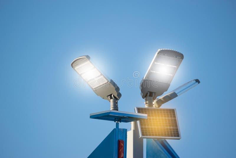与灯的太阳电池板在能量力量概念的天空蔚蓝下 免版税库存照片