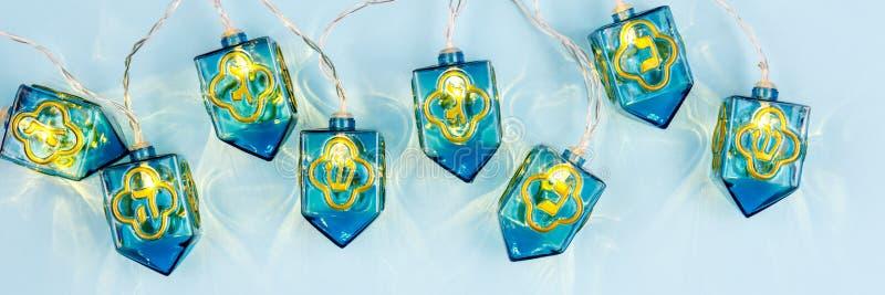 与灯笼dreidels的蓝色背景 光明节和犹太人的holid