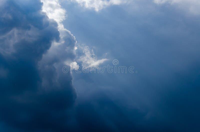 与灰色云彩和太阳光芒的剧烈的天空背景 库存图片