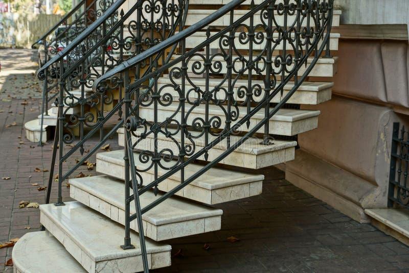 与灰色具体步鄹的楼梯和与一个伪造的样式的铁黑扶手栏杆在边路的墙壁附近 图库摄影