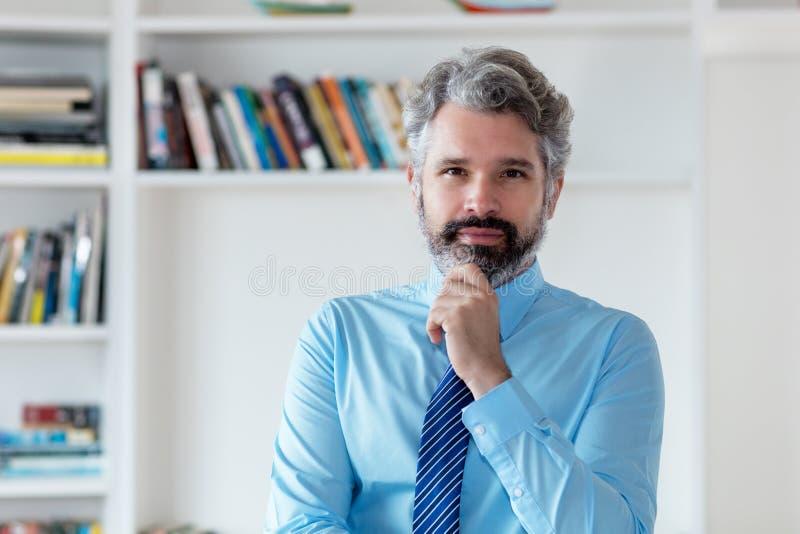 与灰色头发和领带的严肃的商人 库存图片