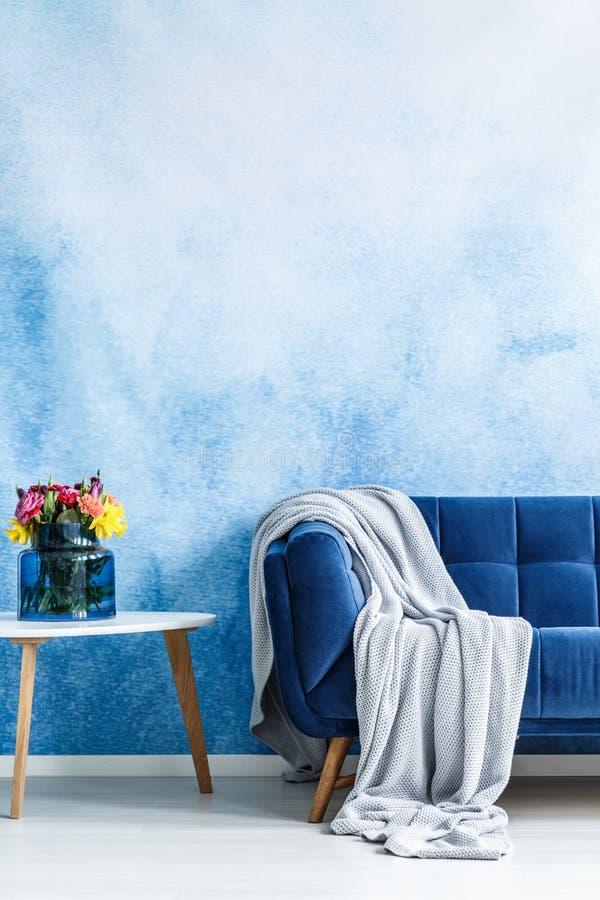 与灰色毯子和小边ta的舒适的深蓝长椅 免版税图库摄影